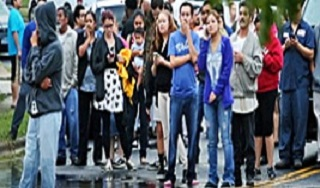 An image of a crowd of students standing observing an incident of a flooded campus