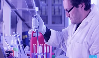 An image of a man in a science lab placing a liquid into test tubes