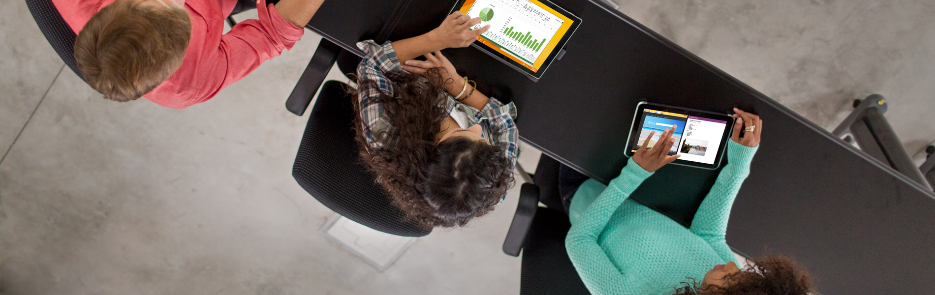 Image of three students sitting beside each other in a lecture theatre, each using their Surface.