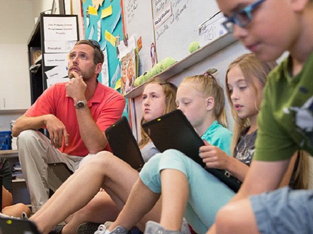 A teacher sat with his students using Windows 10 devices during a classroom exercise.