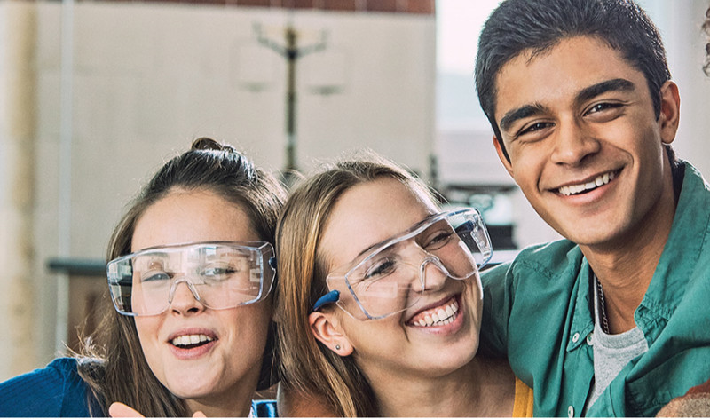 A photograph of four students with their arms round each other smiling, three of them are wearing safety goggles.
