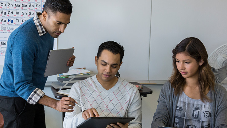 Image of a teacher directing students with holding a Microsoft Surface tablet