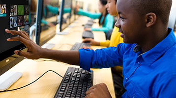 Image of a child using Windows 10 in a touchscreen desktop computer