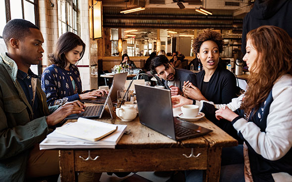 image of five people sitting aroung a table with laptops in a coffee shop