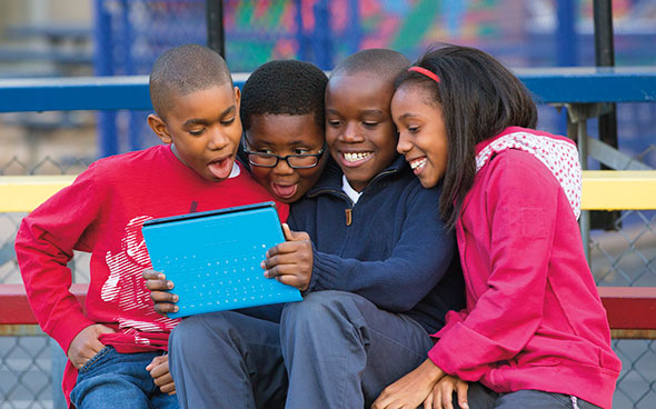 image of four children sitting on a bench sharing a surface tablet