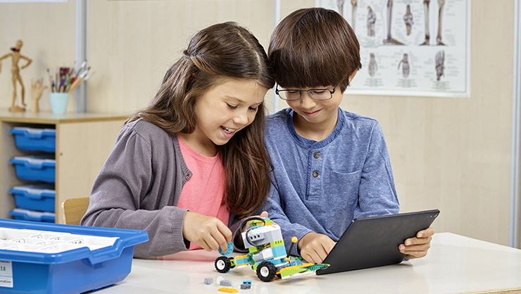 Image of children using a windows Laptop to program a LEGO® robot.