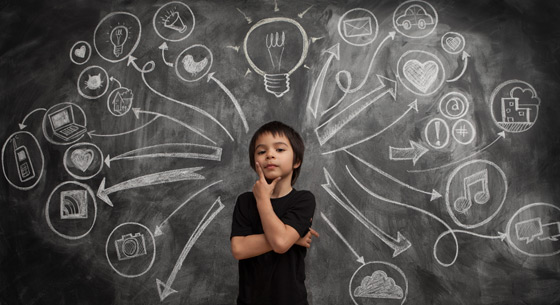 A young boy with his hand on his chin thinking, in front of a chalkboard with thought bubbles coming out from behind him