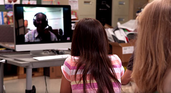 A photograph of a young girl talking to a man using Skype running on a laptop.
