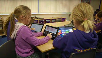 Image of two young children at a table using surface tablets