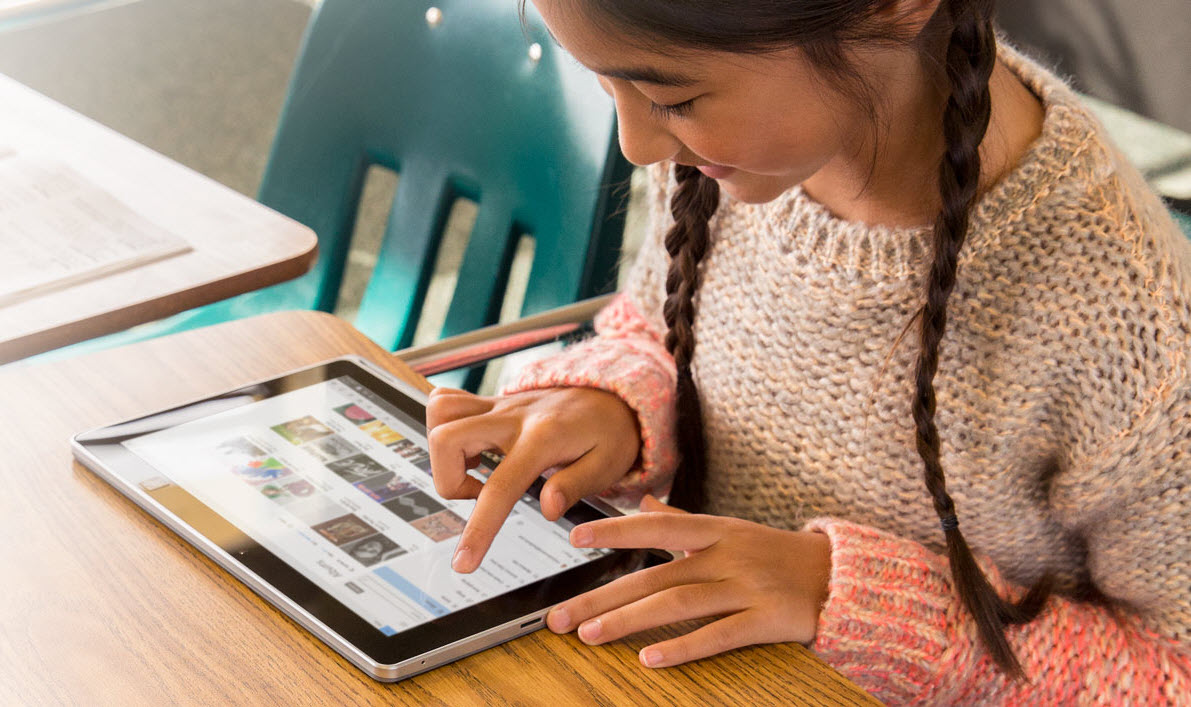 A picture of a young girl using Windows 10 on a Surface.