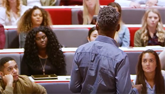 Image of a lecturer standing in a lecturer hall infront of a room full of students